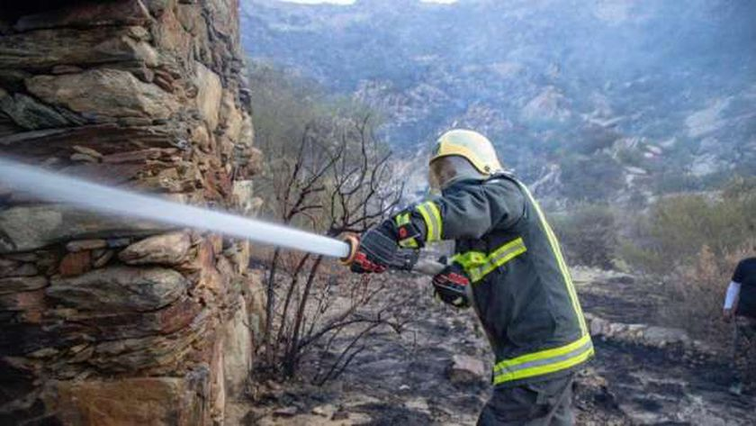 عنصر في الدفاع المدني السعودي يعمل على إطفاء الحريق