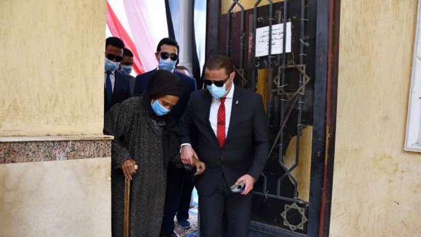 محافظ الفيوم يُساعد مُسنة في الإدلاء بصوتها داخل لجنة انتخابية