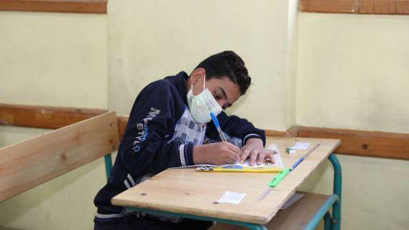 الطلاب يرتدون الكمامات الطبية أثناء تأديتهم امتحانات الفصل الدراسي الأول