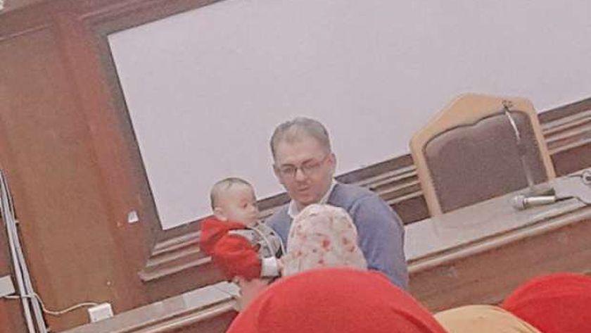 دكتور أحمد عمار وهو يحمل طفل طالبته