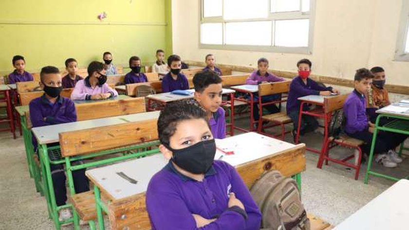 طلاب يرتدون الكمامات الطبية داخل أحد الفصول