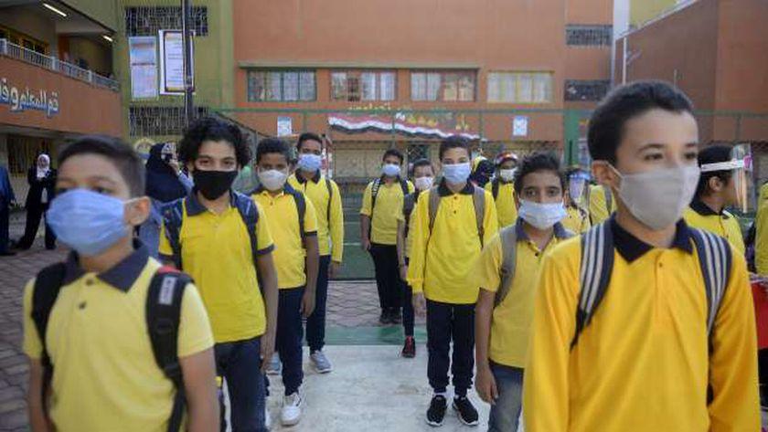 طلاب يرتدون كمامات طبية في طابور الصباح