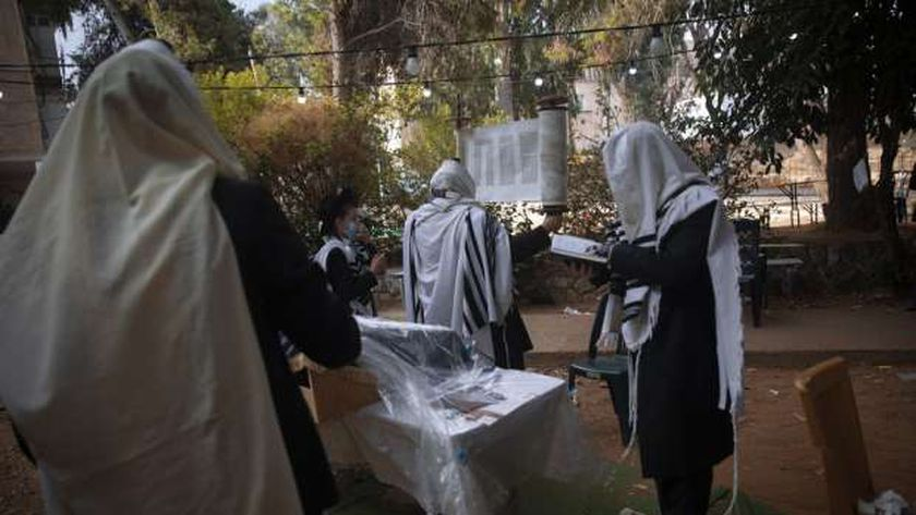 يهود متشددون خلال صلاة الصباح بجوار منازلهم بعد تشديد إجراءات الإغلاق